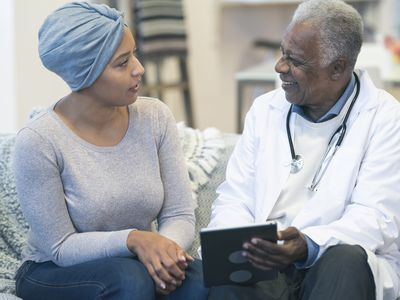 Woman wearing a turban talking to a doctor.