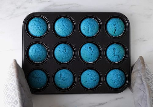 A muffin tin full of bright blue muffins.