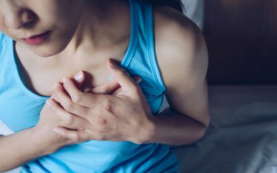 A young woman in a blue tank top (her face is not visible) holding her hands on her chest over her heart.