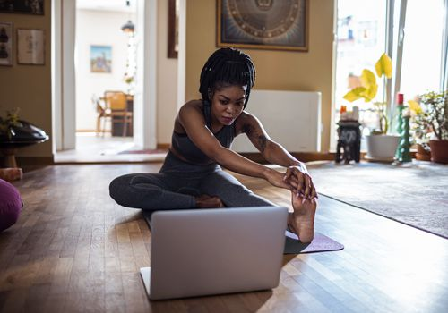 Black woman stretching at home looking at a laptop screen.