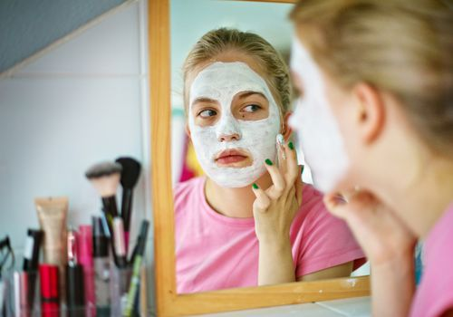 Teenage girl applying face mask while looking in the mirror