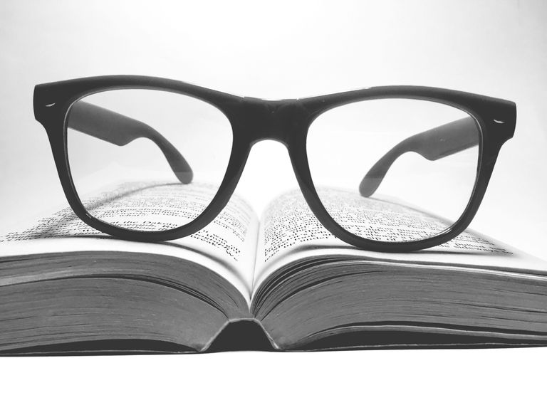 Reading glasses resting on a book