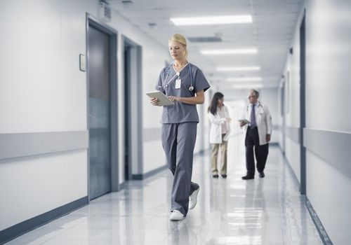 Nurse reading a medical chart while walking down a hospital hallway