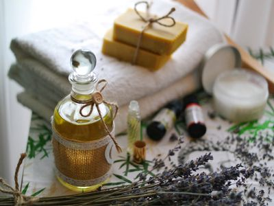 Coconut oil next to lavender and soaps on a towel