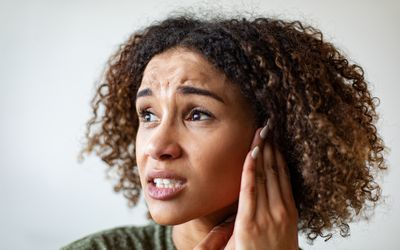 person holding ear