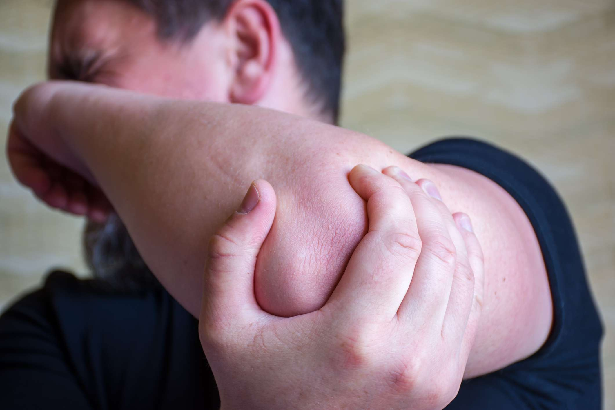 a man holding his elbow and grimacing in pain