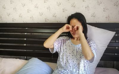 Woman rubbing eyes while sitting on bed at home