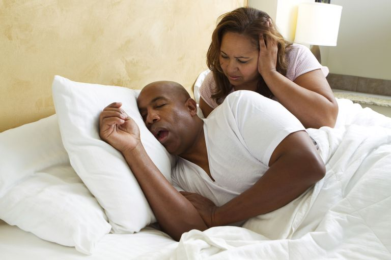 man snoring next to disgruntled wife