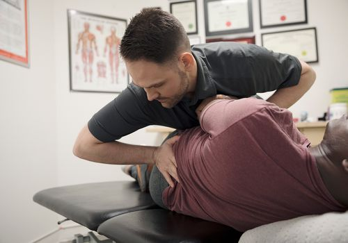 Male physiotherapist stretching client in office