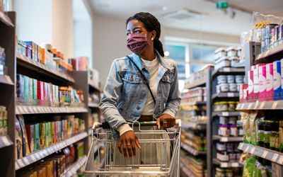 A Black woman wearing protective face mask buying grocery at a supermarket.