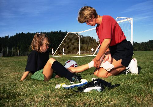 soccer coach bandaging a young player's ankle on the field