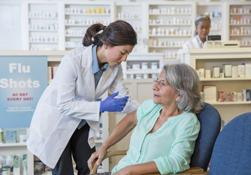 Woman getting a flu shot at a pharmacy