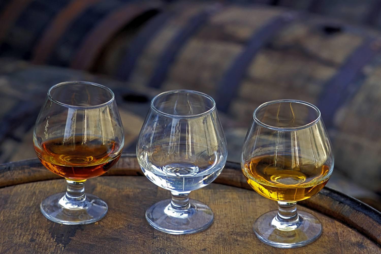 Three glasses of rum on a barrel.