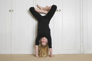 Girl doing a handstand against a wall with her legs bent