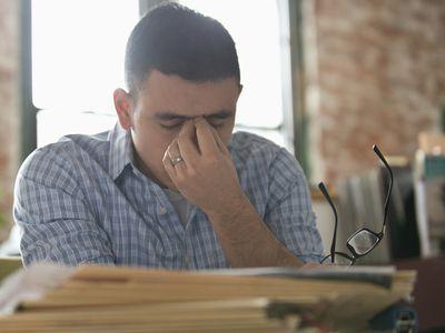 Anxious Hispanic businessman rubbing forehead at office desk