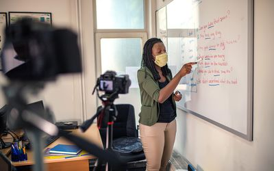 Teacher at a whiteboard during COVID-19 pandemic.
