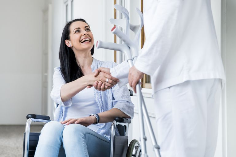 Woman in a wheelchair greeting a doctor