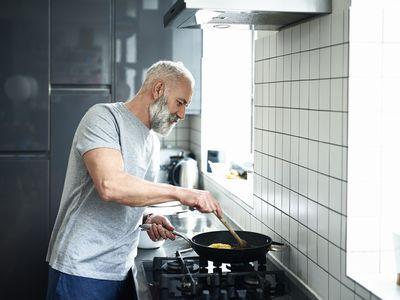 Man with grey beard using frying pan in modern kitchen