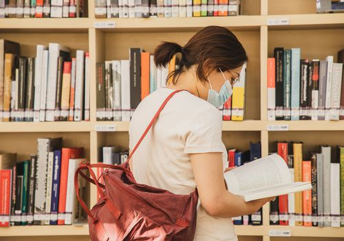 Student wearing a mask looking at a book in a library.