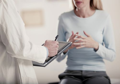 Doctor holding tablet PC talking to patient