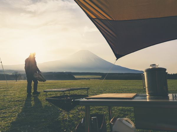 Person standing at the edge of their campsite, mountain in the distance