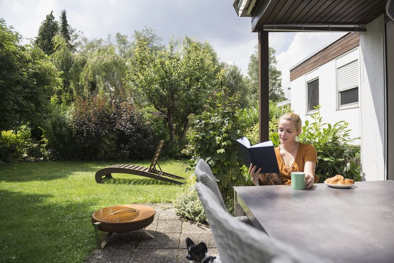 Woman reading in back yard