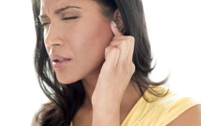 Woman touching ear in pain.