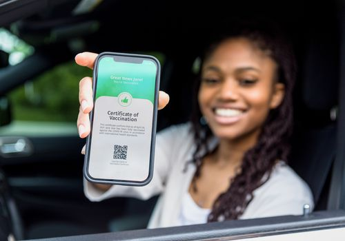 """A young Black woman in a car holding up her phone with has a """"Certificate of verification"""" for her COVID vaccine status."""