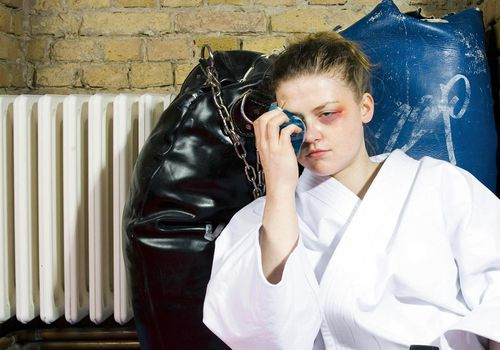 woman in martial arts gi holding ice pack up to her eye