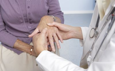 A doctor examines a patient's hand