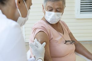Older woman receiving a flu shot in the arm.