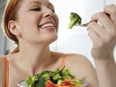 Young woman eating salad, head and shoulders