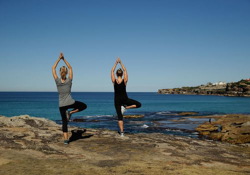 Two women doing tree pose next to the ocean