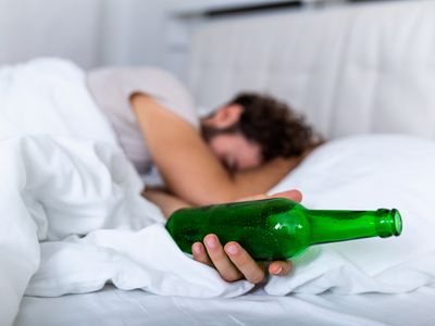 After drinking. Drunk bearded adult man lying on the bed and sleeping after drinking lots of alcohol, Empthy bottle on the bed, alcoholism, alcohol addiction and people concept