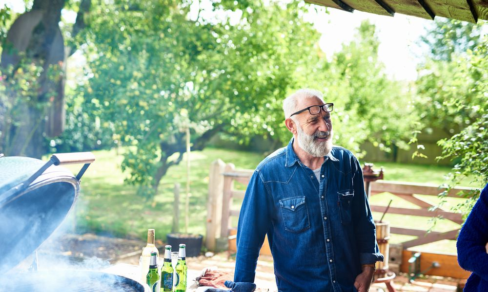 Cheerful mature man smiling by bbq in garden