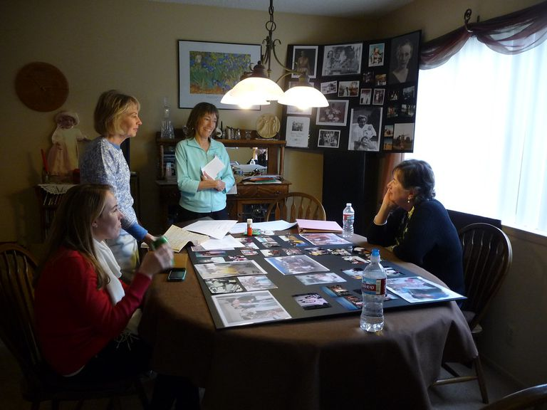 4 women around a table making funeral memory boards