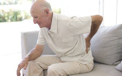 elderly Man rubbing aching back
