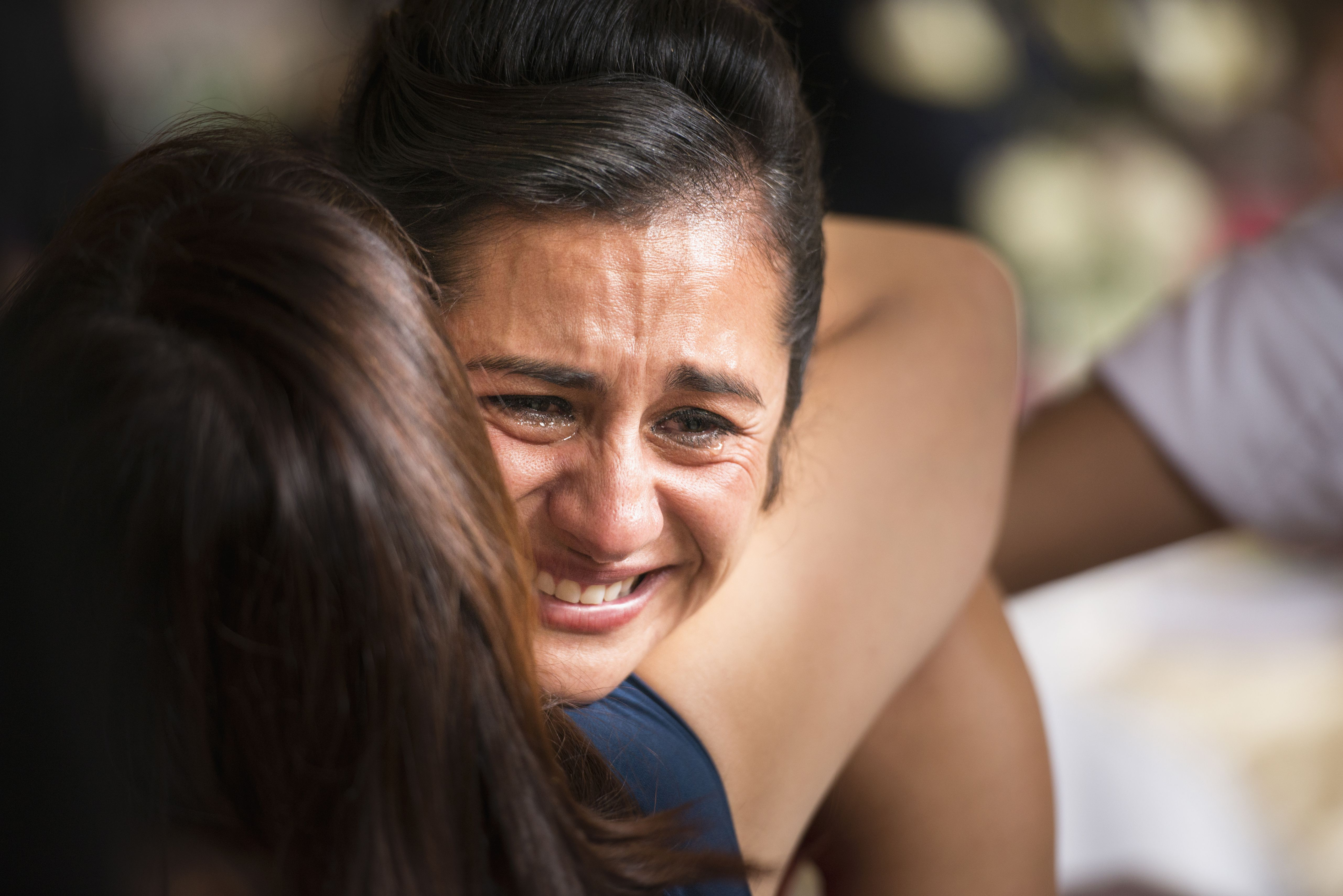 Hispanic woman crying being hugged by another woman