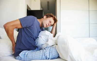 A man in bed with lower back pain