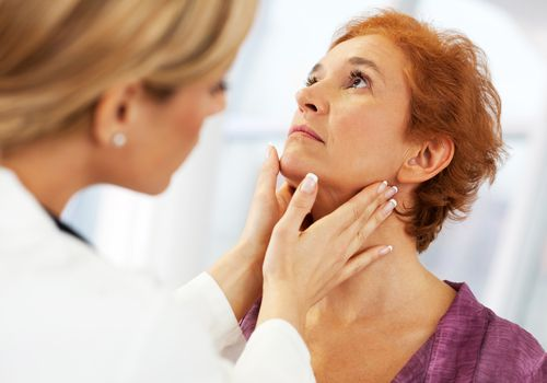 doctor examining a female patient's neck