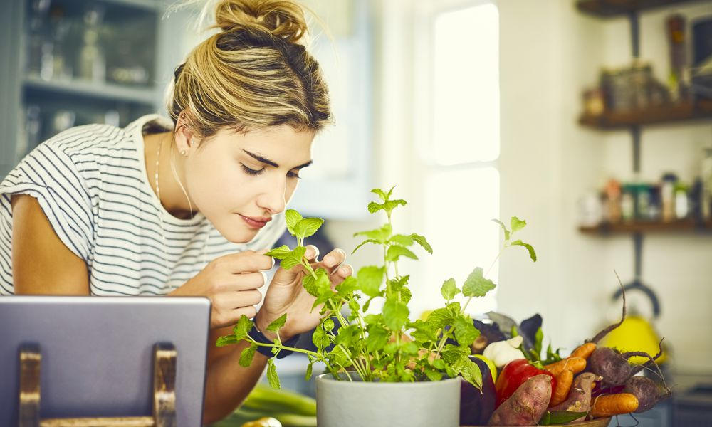 Young woman smelling mint leaves by digital tablet