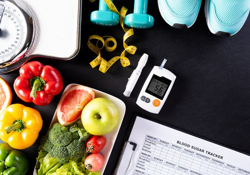 fresh fruits, vegetables, weight scale, sports shoes, dumbells, measure tape and diabetic measurement set on black background