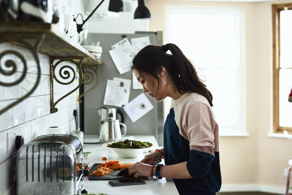 Woman cooking and cutting carrots