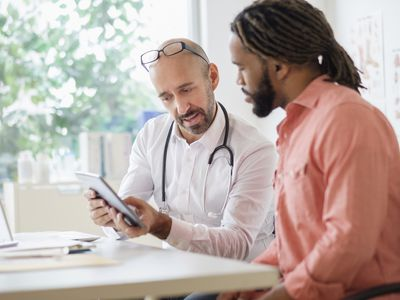 Doctor giving consultation to patient using digital tablet