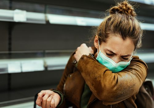 Woman sneezing into arm with face mask.