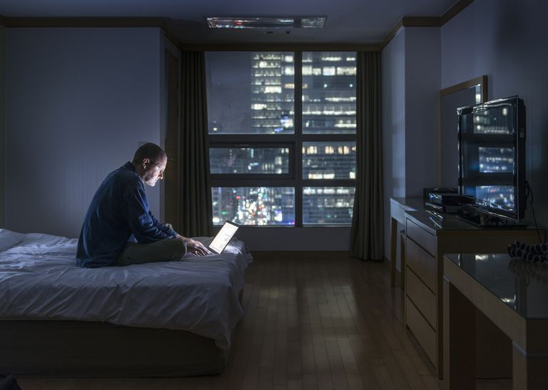 Man using laptop at night in bed may contribute to insomnia due to artificial light exposure