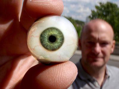 Man holding an artificial eye
