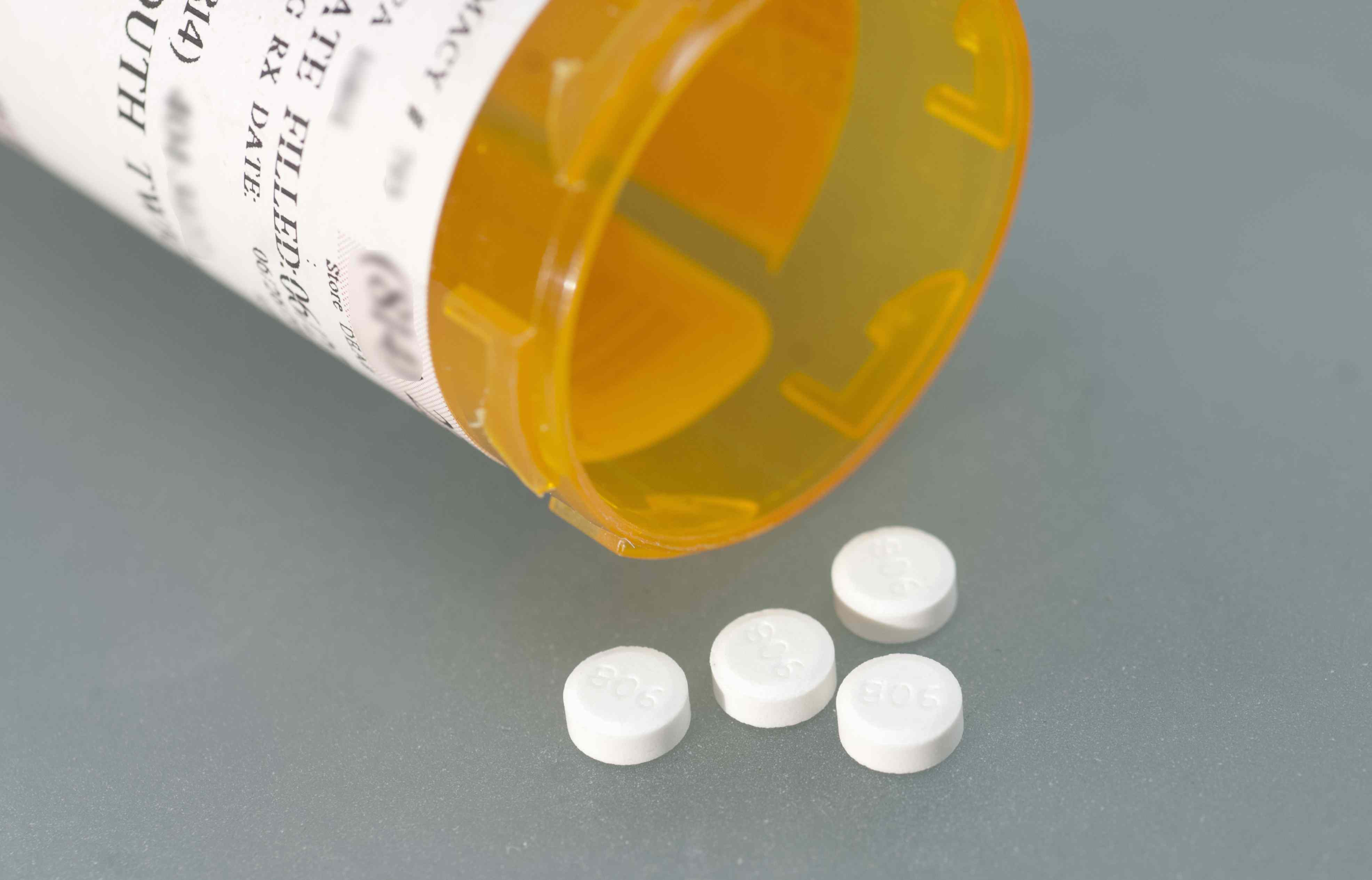 Open prescription bottle with four white pills laying on a gray background