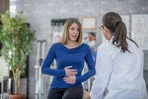 Woman with stomach flu talking to her doctor