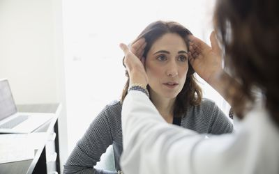 Plastic surgeon consulting female patient in doctors office